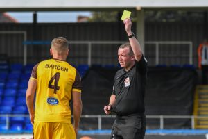 referee holds yellow card up