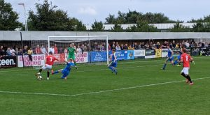 FC United player takes shot in match vs Bootle
